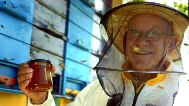 HD Super Slow-Mo: Portrait Of A Beekeeper HD1080p: Super Slow Motion shot of a beekeeper in protective clothing posing with a glass of honey in front of a beehive. hobbies stock videos & royalty-free footage
