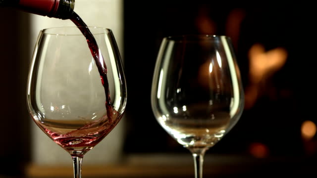 HD Super Slow-Mo: Pouring A Red Wine HD1080p: Super Slow Motion shot of an unrecognizable person pouring a red wine into a wine glass by the fireplace. red wine stock videos & royalty-free footage
