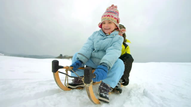 stockvideo's en b-roll-footage met hd super slow-mo: siblings sledging down the hill - family winter holiday