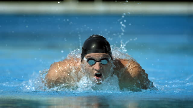 hd super slow-mo: swimmer performing the butterfly stroke - competition stok videoları ve detay görüntü çekimi