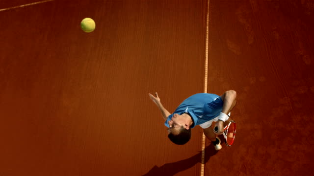hd super slow-mo: tennis player serving on the clay court - competition stok videoları ve detay görüntü çekimi