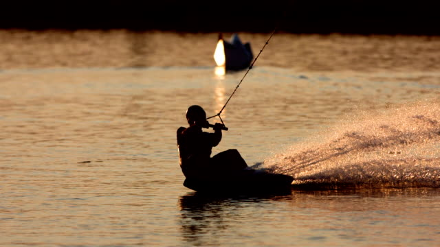 HD Super Slow-Mo: Wakeboarder Performing Body Slide At Sunset video
