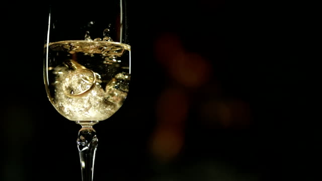 HD Super Slow-Mo: Wedding Rings In Glass Of Champagne