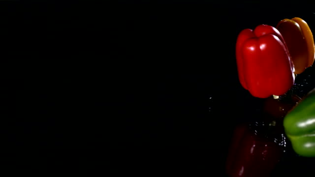 vídeos de stock e filmes b-roll de hd super em câmara lenta: molhado bell peppers caindo sobre fundo preto - red bell pepper isolated