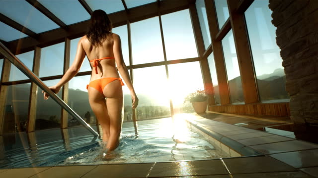 hd super slow-mo: woman getting into the pool at sunset - affluent lifestyles stock videos & royalty-free footage
