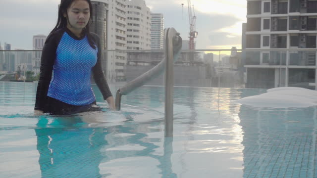 hd super slow-mo: frau bekommen auf den pool bei sonnenuntergang. - nass stock-videos und b-roll-filmmaterial
