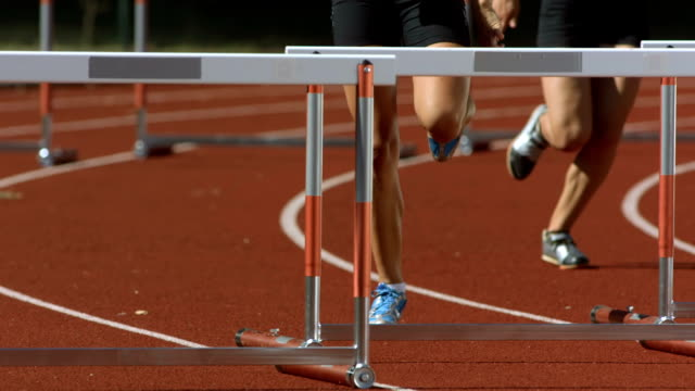 hd super slow-mo: women sprinting the hurdle race - track and field stock videos and b-roll footage