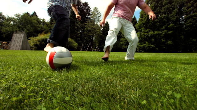 hd super slow-mo: young boy playing soccer with father - gräsmatta odlad mark bildbanksvideor och videomaterial från bakom kulisserna