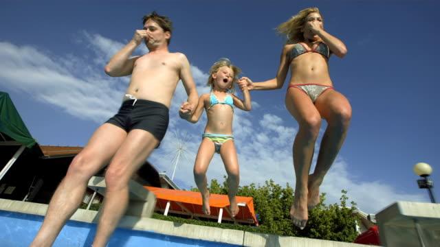vídeos de stock e filmes b-roll de hd super em câmara lenta: família jovem saltar na piscina - jump pool, swimmer