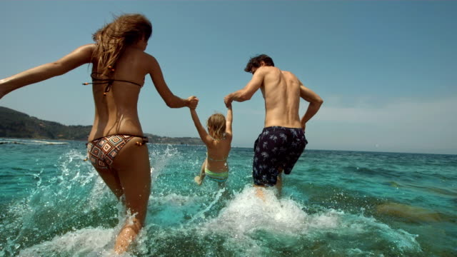 HD Super Slow-Mo: Young Family Splashing Into The Sea video