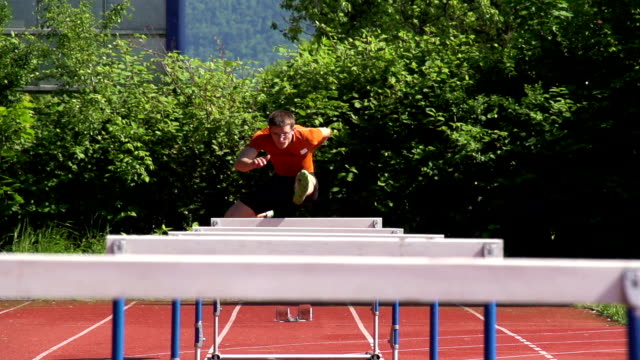 hd super slow-mo: young man at hurdle race 110m - track and field stock videos and b-roll footage