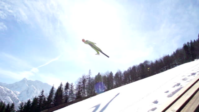 hd super slow-mo: young man performing ski jump - vintersport bildbanksvideor och videomaterial från bakom kulisserna