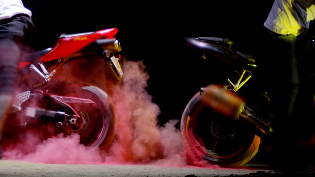 super sport motorcycle doing a tire burnout with colorful sand, holi. shot on red epic cinema camera in slow motion. - burnout filmów i materiałów b-roll