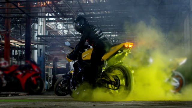 super sport motorcycle doing a tire burnout with colorful sand. slow motion. - burnout filmów i materiałów b-roll
