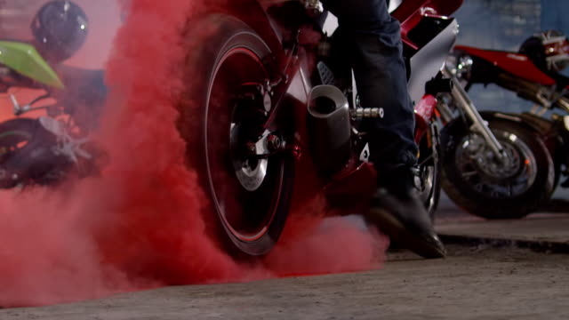 Super sport motorcycle doing a tire burnout with colorful sand. Sportbike doing a tire burnout with colorful sand, holi. Shot on RED EPIC Cinema Camera in slow motion. motorcycle stock videos & royalty-free footage