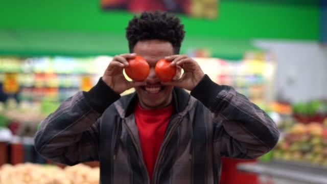 supermarkt-kunden haben spaß mit tomaten - tomate stock-videos und b-roll-filmmaterial