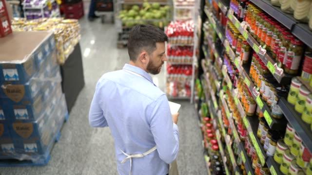 stockvideo's en b-roll-footage met supermarktmedewerker of eigenaar die en digitale tablet loopt gebruiken - buiten de vs