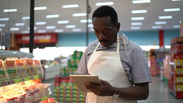 vídeos de stock e filmes b-roll de supermarket employee walking and using tablet - supermarket worker