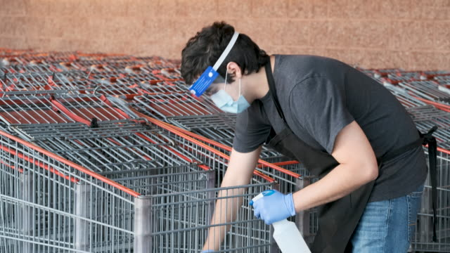 vídeos de stock e filmes b-roll de supermarket employee wearing masks and latex gloves disinfecting shopping carts due contagion prevention - supermarket worker