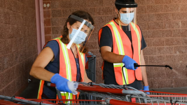 vídeos de stock e filmes b-roll de supermarket employees wearing masks and latex gloves disinfecting shopping carts due contagion prevention - supermarket worker