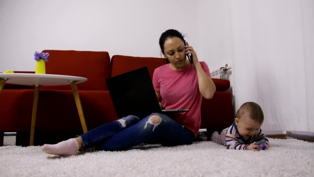 vídeos de stock e filmes b-roll de supermum multitasking at home with baby son - baby super hero