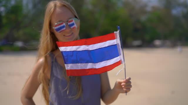 vídeos y material grabado en eventos de stock de disparo de superslowmotion de una hermosa joven con unas gafas de sol reflectantes sostiene una bandera nacional de tailandia de pie en una playa - baile de estudiantes de secundaria