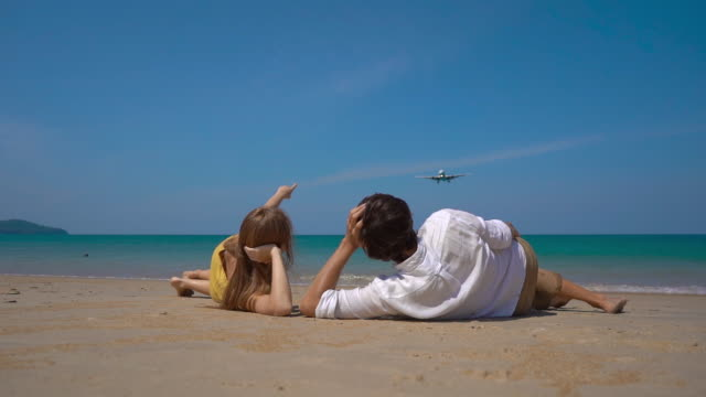 Superslowmotion shot of a happy man and woman tourists laying on a beautifull beach watching a landing airplane Superslowmotion shot of a happy man and woman tourists laying on a beautifull beach watching a landing airplane. landing touching down stock videos & royalty-free footage