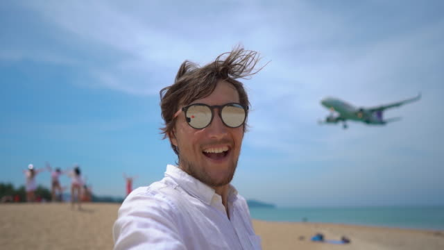 Superslowmotion shot of a happy tourist have fun on a tropical beach with an airplane flying over him Superslowmotion shot of a happy tourist have fun on a tropical beach with an airplane flying over him. landing touching down stock videos & royalty-free footage