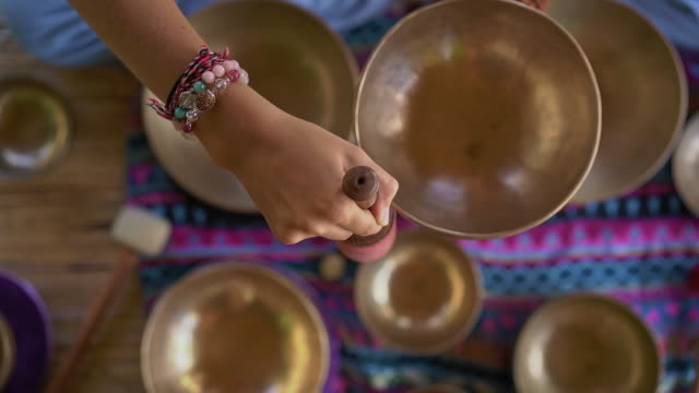 Superslowmotion shot of a woman master of Asian sacred medicine performs Tibetan bowls healing ritual. Meditation with Tibetan singing bowls. She sits in a gazebo for meditation with a beautiful waterfall in the background