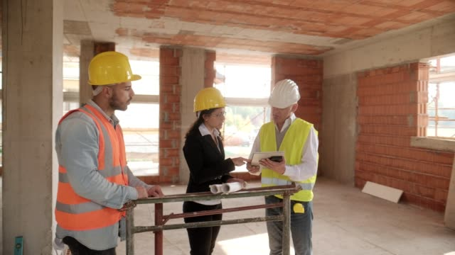 vidéos et rushes de ingénieur superviseur et réunion de travailleur manuel en chantier - hlm
