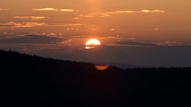 Superzoom plan timelapse sunset through sunset clouds in orange tones. Low key