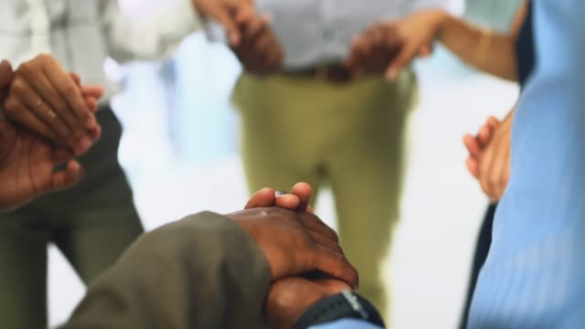 Support each other to success 4k video footage of a group businesspeople joining their hands in solidarity in a modern office prayer stock videos & royalty-free footage