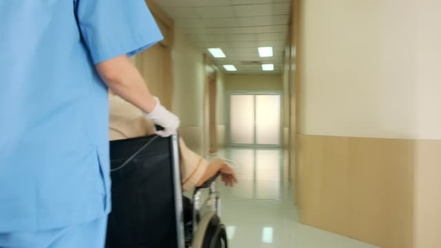 病院の廊下を通って車椅子で古いアジアの患者を移動する看護師をサポートします。手順を実行しています。フレンドリーなスタッフと暖かく鮮度の病院.ヘルスケアとアイデアの概念 - 老人ホーム点の映像素材/bロール