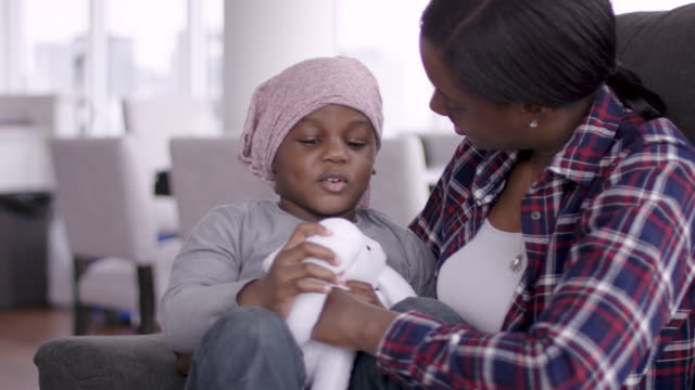 Supportive mother holds child with cancer A young black mother lovingly holds her child who is fighting cancer. The child is wearing a bandana. The two individuals are smiling. They are filled with gratitude and hope for recovery. cancer illness stock videos & royalty-free footage