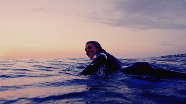 Surf girl paddles by camera and splashes water while on surfboard on a California summer night shot in slow motion at sunset.