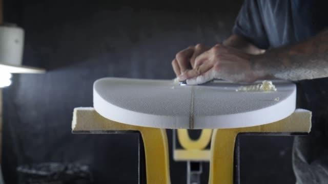 stockvideo's en b-roll-footage met de productie van de surfplank, shaper die stringer op een surfplank snijdt. - sportartikelen