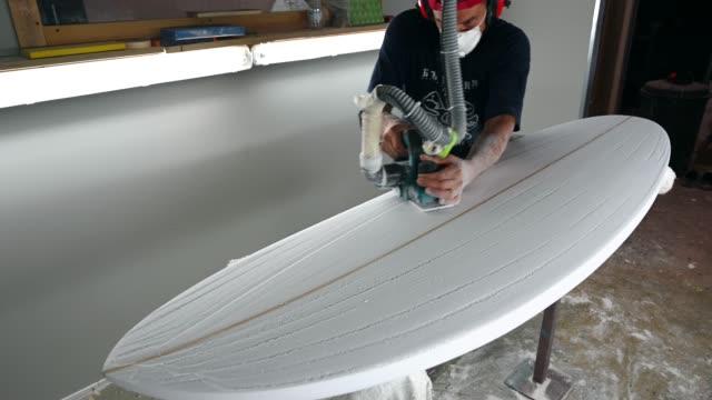 warsztaty modelowania desek surfingowych - człowiek kształtujący deskę surfingową z szlifierką - sprzęt sportowy filmów i materiałów b-roll