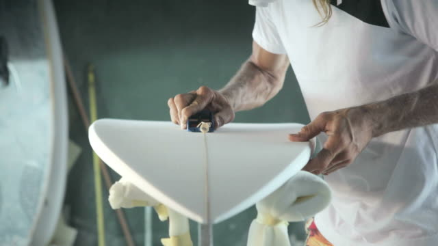 Surfboard shaping, Shaper cutting down the stringer on a surfboard Surfboard shaping, Shaper working on a board molding a shape stock videos & royalty-free footage