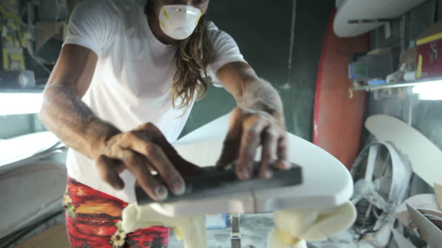 surfboard shaping, shaper sanding the nose of the surfboard with a sanding block - levigatrice video stock e b–roll