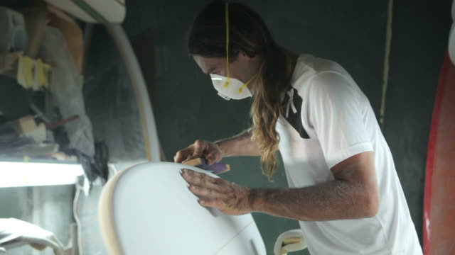 surfboard shaping, shaper using a foam sander to shape the side of the surfboard - levigatrice video stock e b–roll
