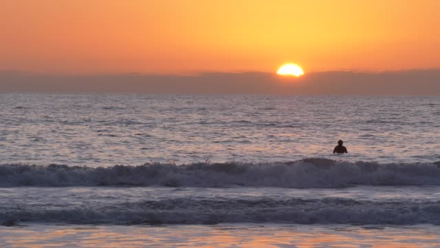 surfer at Scenic orange pink Sunset with epic rays of light and sun flare wooden pier in San Clementa California
