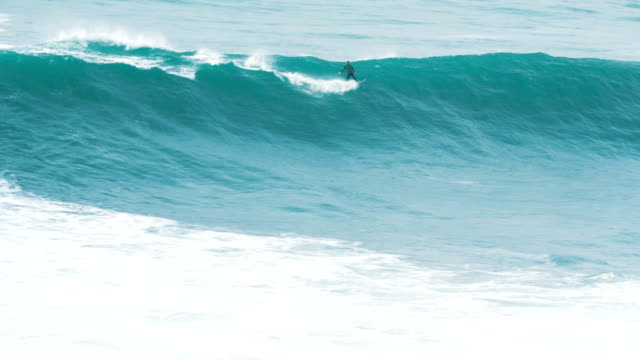 surfer caught a giant wave and confidently rides a surf, slow motion