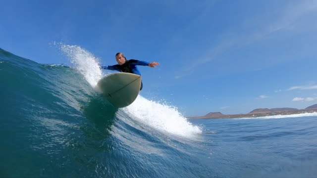 SLOW MOTION: Surfer dude making a sharp turn on surfboard and splashes camera. video