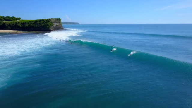 AERIAL: Surfer falling off the surfboard when riding a big wave in sunny Bali video