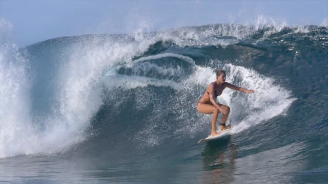 SLOW MOTION: Surfer girl in bikini riding big barrel overhead waves on sunny day video