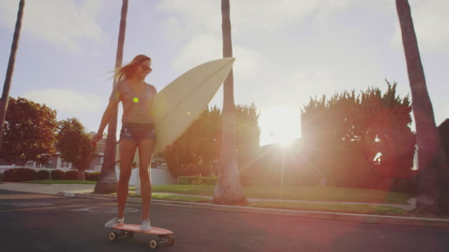 Surfer girl riding skateboard down street at sunset with lens flare 4k lifestyle clip of happy attractive surfer girl lifestyle on California beach shot on RED camera california stock videos & royalty-free footage