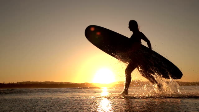 SLOW MOTION: Surfer girl running in shallow ocean splashing water at sunset