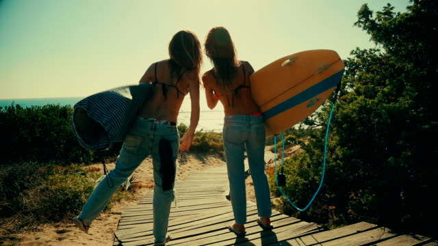 Surfer girls high-five and go to the waves video