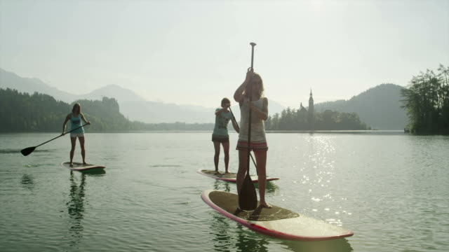 SLOW MOTION: Surfer girls SUPing on beautiful lake at sunrise video