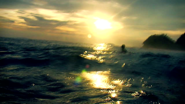 surfer in water watching sunset video